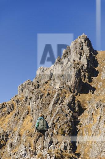Italy, Como, woman on a hiking trip in the mountains looking at summit