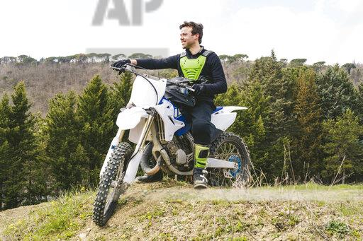 Portrait of confident motocross driver on circuit