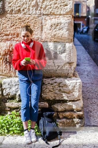 Young woman wearing red pullover, using smartphone in Verona