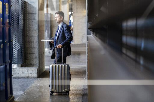 Businessman with suitcase standing on station platform
