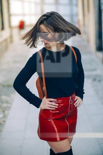 Smiling young woman wearing red patent leather skirt with zipper tossing her hair