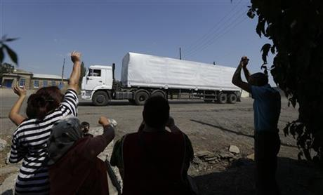 Ukrainian people greet the first truck as it passes the border post at Izvaryne, eastern Ukraine, Friday, Aug. 22, 2014. The first trucks in a Russian aid convoy crossed into eastern Ukraine on Friday, seemingly without Kiev's approval, after more than a week's delay amid suspicions the mission was being used as a cover for an invasion by Moscow. (AP Photo/Sergei Grits)