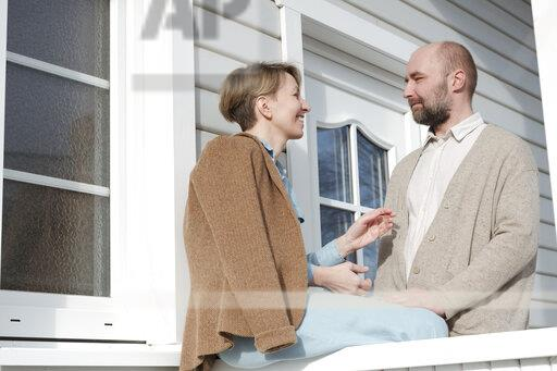 Happy couple talking on porch of their house