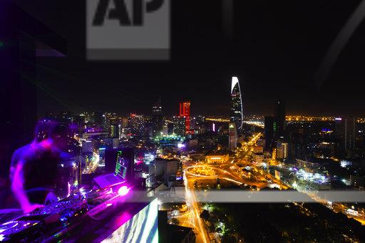 Vietnam, Ho Chi Minh City at night, DJ in the foreground