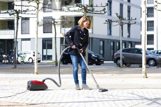 Woman using vacuum cleaner on pavement in the city