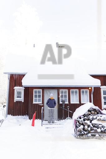 Finland, Kuopio, woman standing in front of farmhouse in winter