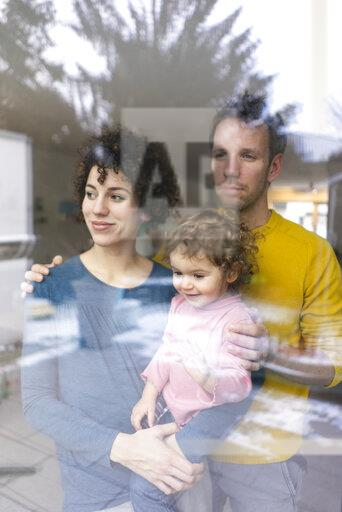 Happy family looking out of window, mother carrying daughter
