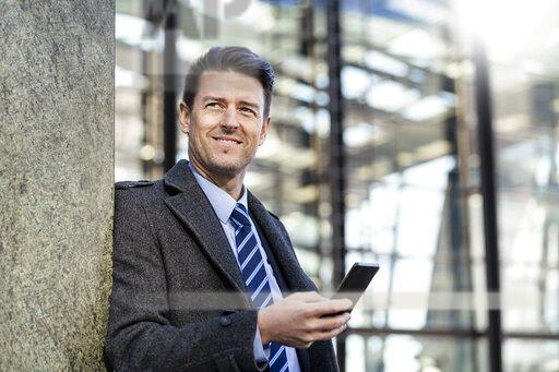 Smiling businessman with cell phone leaning against a wall