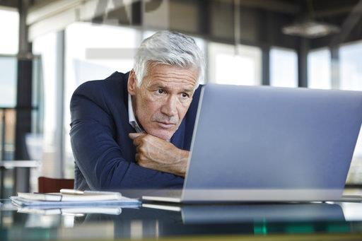 Businessman sitting at desk, trying to solve a problem