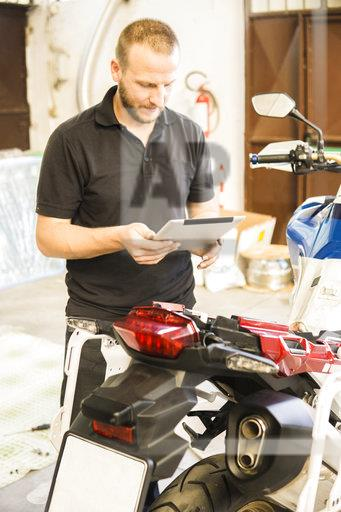Man using tablet next to motorcycle in workshop