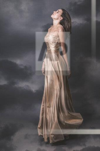 Young woman wearing nude-colored evening dress