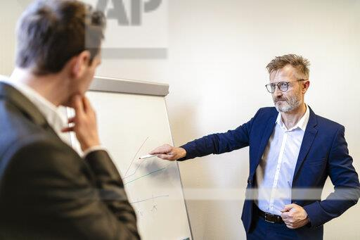 Two businessmen in office discussing at flip chart