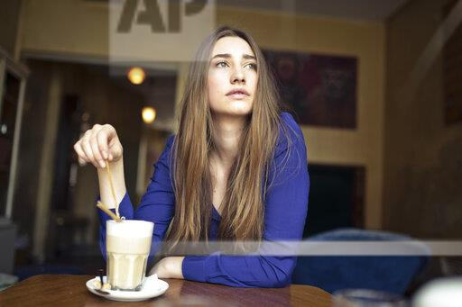 Young woman sitting at table in a cafe looking sideways