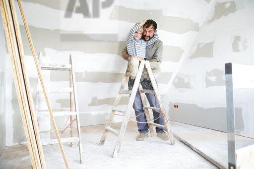 Portrait of happy father and son working on loft conversion