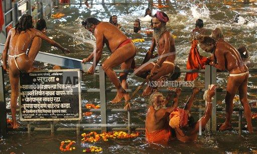 Naga sadhus, or naked Hindu holy men take holy dip in the Godavari River during Kumbh Mela, or Pitcher Festival, at Trimbakeshwar in Nasik, India, Saturday, Aug. 29, 2015. Hindus believe taking a dip in the waters of a holy river during the festival, will cleanse them of their sins. According to Hindu mythology, the Kumbh Mela celebrates the victory of gods over demons in a furious battle over a nectar that would give them immortality.