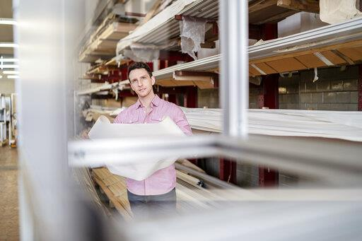 Man with plan in factory warehouse