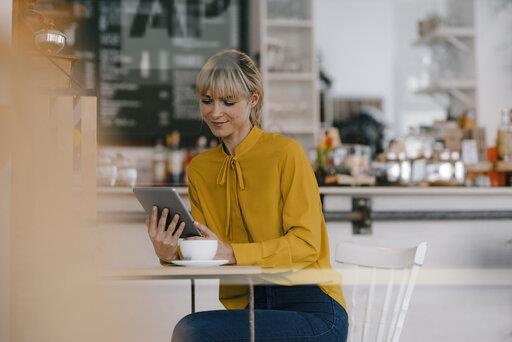 Blond businesswoman using smartphone in a coffee shop, reading text messages