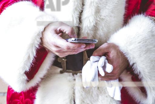 Hand of Santa Claus text messaging, close-up