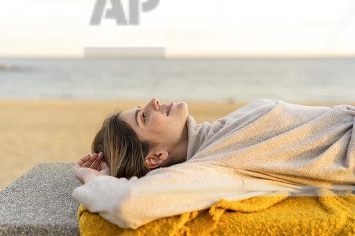 Young woman looking up while lying on bench at beach promenade during sunset