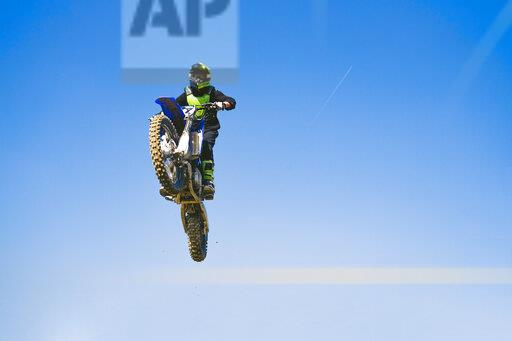 Motocross driver jumping in blue sky