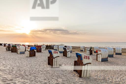 Germany, Lower Saxony, Cuxhaven, Duhnen, beach with hooded beach chairs at sunrise