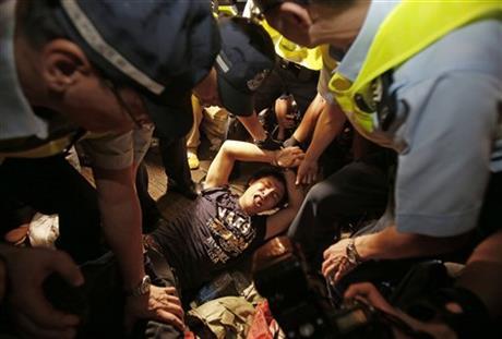 A man is cuffed by police and taken from the confrontation of pro-democracy student protesters and angry local residents in Mong Kok, Hong Kong, Friday, Oct. 3, 2014. Pushing and yelling, hundreds of Hong Kong residents tried to force pro-democracy activists from the streets they were occupying Friday as tensions rose in the weeklong protests that have shut down parts of the city.