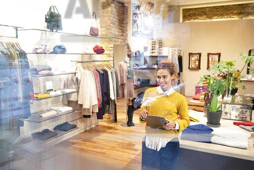 Young woman working in fashion store, using laptop