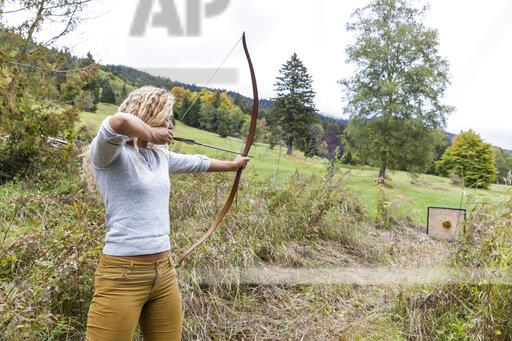 Archeress aiming with her bow on target