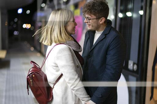 Happy young couple standing at tram stop in the evening looking at each other