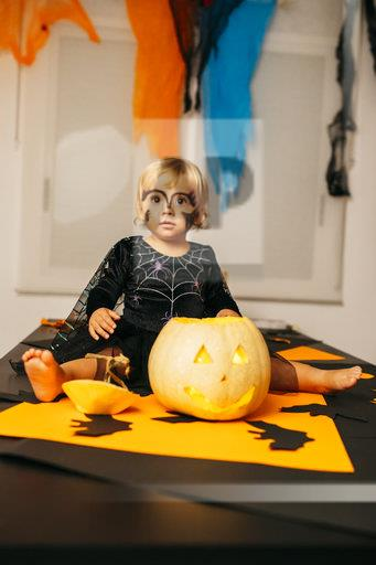 Portrait of little girl with painted face and fancy dress sitting on table with Jack O'Lantern