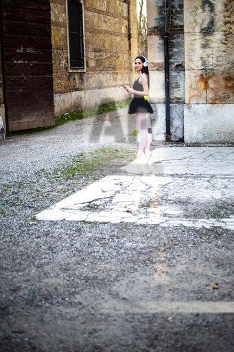 Italy, Verona, woman in ballet dress with cell phone and headphones standing at an old building