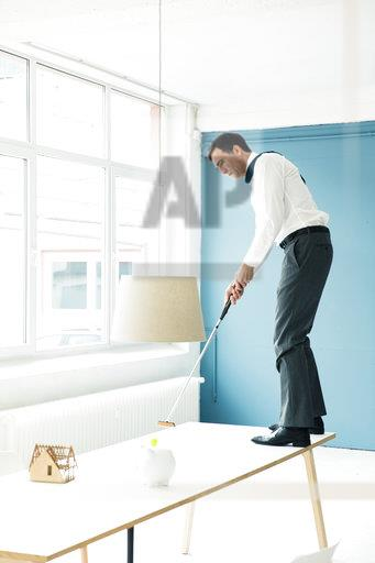 Businessman playing golf on table in office
