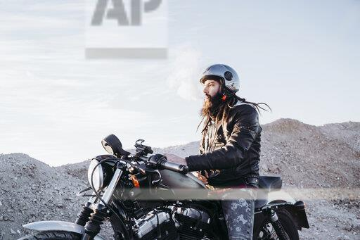 Bearded man with dreadlocks sitting on motorbike smoking electronic cigarette