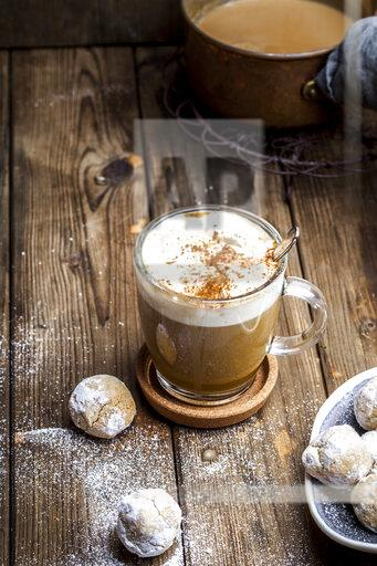 Pumpkin spice latte with a dollop of cream and some cookies