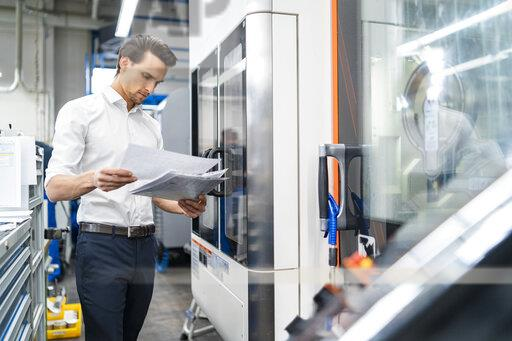 Businessman reading manual at a machine in a factory