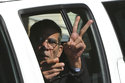 FILE - In this March 30, 2016 file photo, Seif Eddin Mustafa flashes the victory sign from inside a police car after leaving court for a remand hearing in the Cypriot coastal town of Larnaca. Egypts chief prosecutor says Cyprus extradited Mustafa, the hijacker of an EgyptAir plane that was diverted to the Mediterranean island in 2016. Prosecutor Nabil Sadek said late Saturday, Aug. 18, 2018, that Egyptian police have taken custody of Seif Eddin Mustafa in the Cypriot capital, Nicosia. (AP Photo/Petros Karadjias, File)