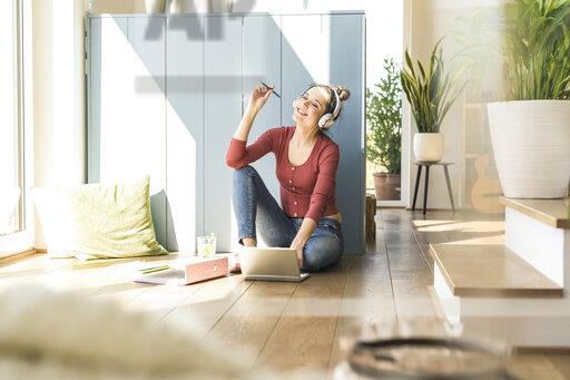 Woman with headphones sitting at the window at home using laptop