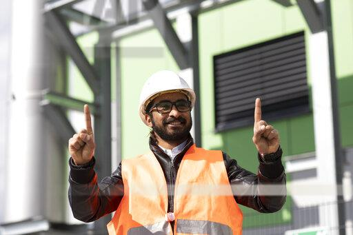 Portrait of construction engineer in front of power station wearing hard hat and safety vest