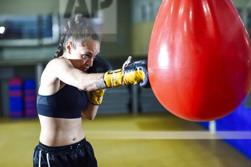 Female boxer training at punch bag in gym