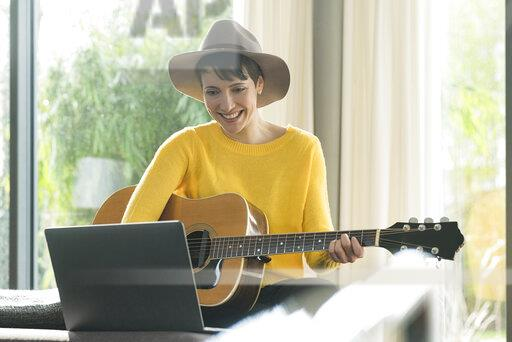 Portrait of smiling woman sitting on couch with guitar looking at laptop