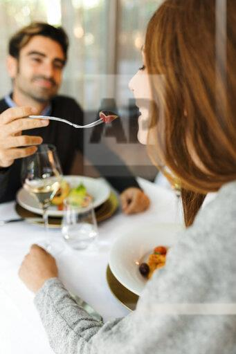 Mman letting woman taste the food in a restaurant