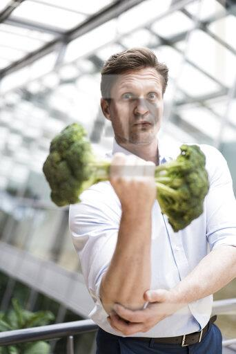 Businessman doing weight training with broccoli
