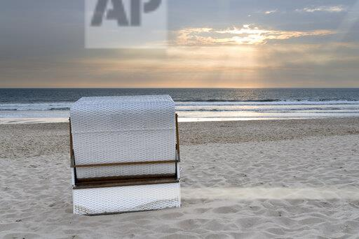 Germany, Sylt, North Sea, sandy beach with hooded beach chair in sunset