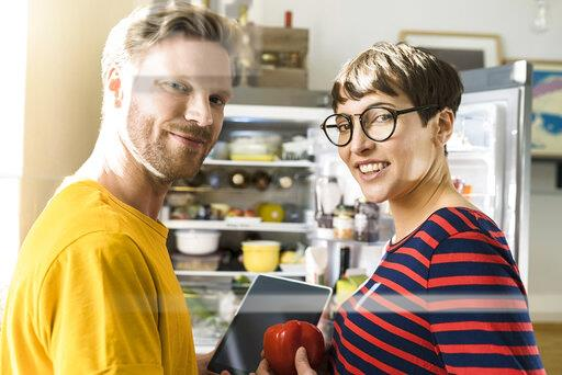 Portrait of couple with tablet in front of their fridge doing online shopping for groceries