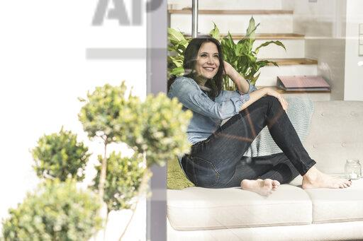 Happy woman sitting on couch behind windowpane at home