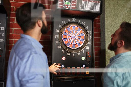 Two men playing darts setting electronic dartboard