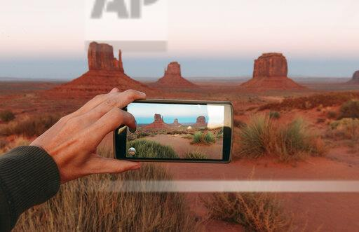 USA, Utah, Monument Valley at sunset, woman's hand taking a photo with mobile