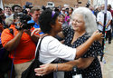 Susan Bro, right, mother of Heather Heyer who was killed during last year's Unite the Right rally, embraces a supporter after laying flowers at the spot her daughter was killed in Charlottesville, Va., Sunday, Aug. 12, 2018. Last year, white supremacists and counterprotesters clashed in the city streets before a car driven into a crowd struck and killed Heyer. (AP Photo/Steve Helber)