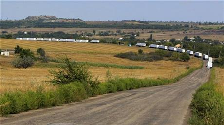 The first trucks of the convoy roll on the main road to Luhansk near the village of Uralo-Kavkaz, after it passed the border post at Izvaryne, eastern Ukraine, Friday, Aug. 22, 2014. The first trucks in a Russian aid convoy crossed into eastern Ukraine on Friday, seemingly without Kiev's approval, after more than a week's delay amid suspicions the mission was being used as a cover for an invasion by Moscow. (AP Photo/Sergei Grits)