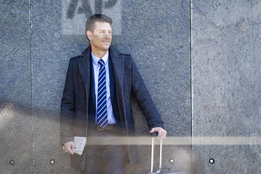 Smiling businessman with suitcase standing at a wall